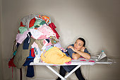 Woman looking at heap of clothes on ironing board