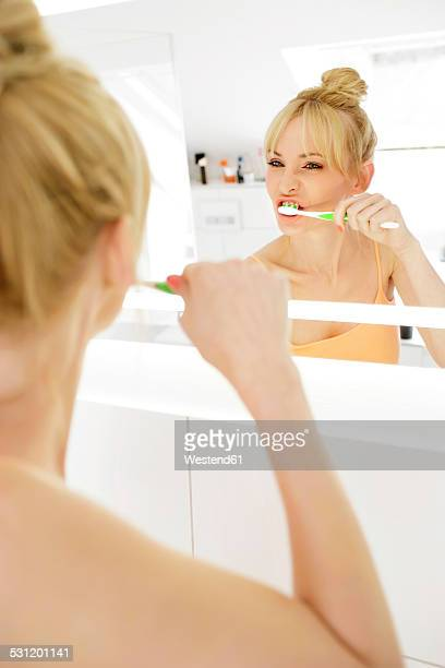 Woman looking at her mirror image while brushing teeth