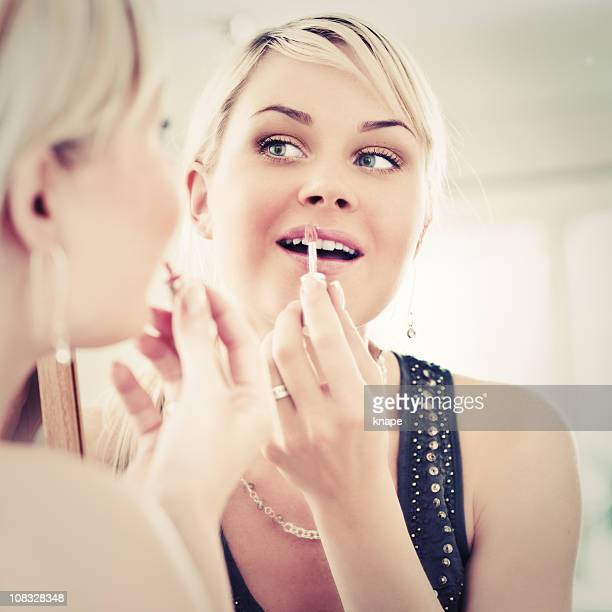 Woman looking at herself in a mirror applying lip gloss