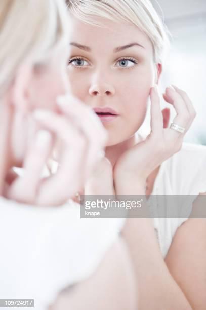 Femme elle-même en regardant dans le miroir
