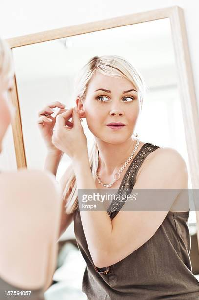 Woman looking at herself in a mirror trying on earrings