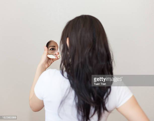 Woman looking at herself in small hand mirror