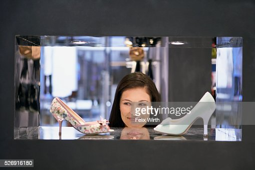 Woman looking at high heel shoes : Stockfoto