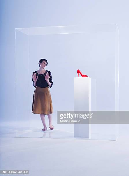 Woman looking at high heels on pedestal in glass cabinet