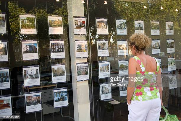 CONTENT] Woman looking at houses for sale in an estate agent's window London England UK
