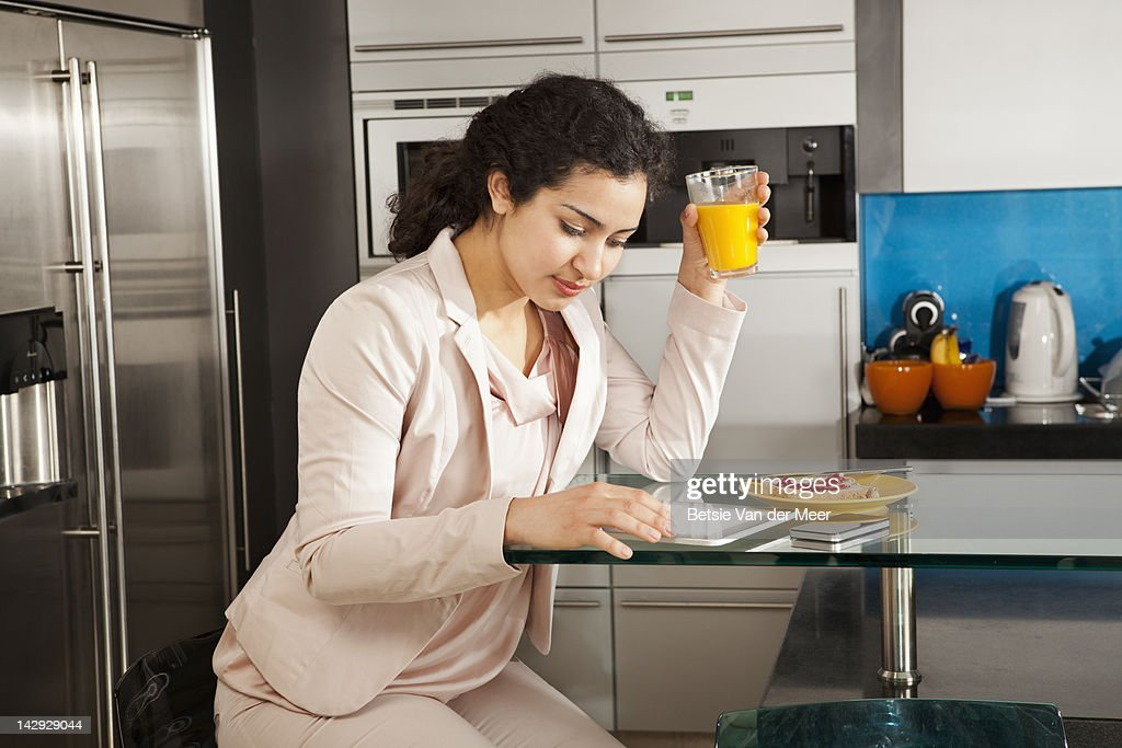 Woman looking at i pad while having breakfast. : Stock Photo