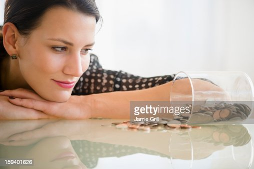 Woman looking at jar of money : Bildbanksbilder