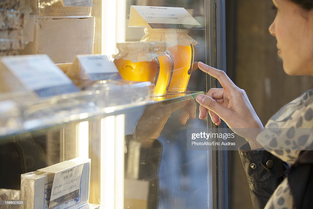 Woman looking at jars of honey in shop window : Stock Photo