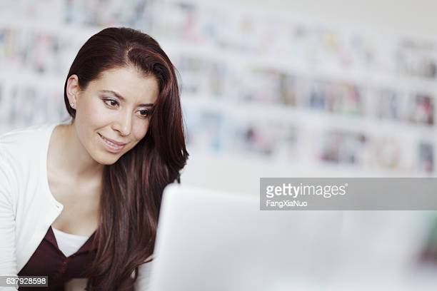 Woman looking at laptop computer in design studio office