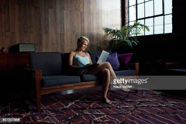 Woman looking at laptop, while sitting in sofa