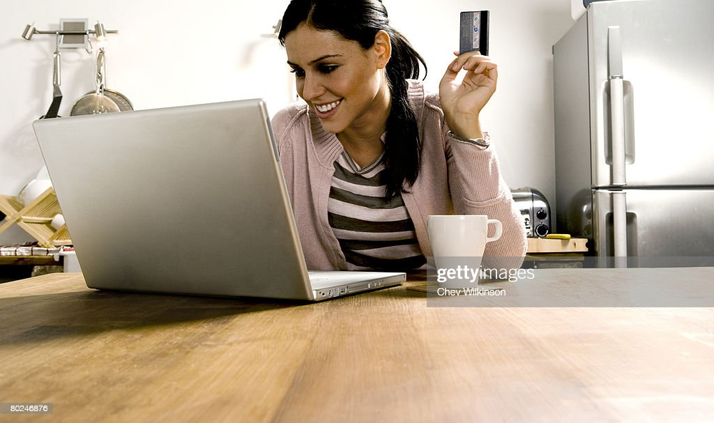 Woman looking at laptop with credit card.
