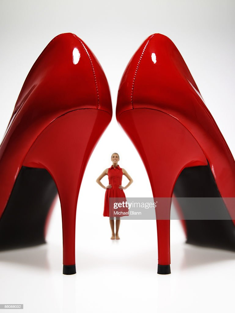 Woman looking at large red heels : Photo