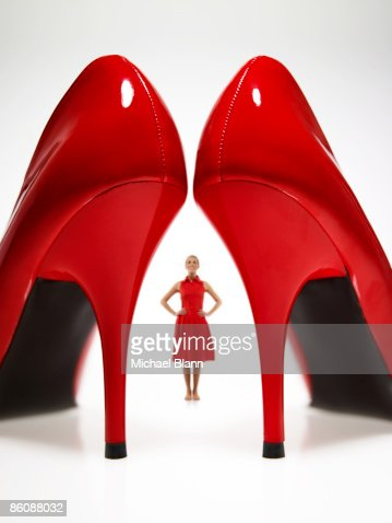 Woman looking at large red heels : Stock Photo