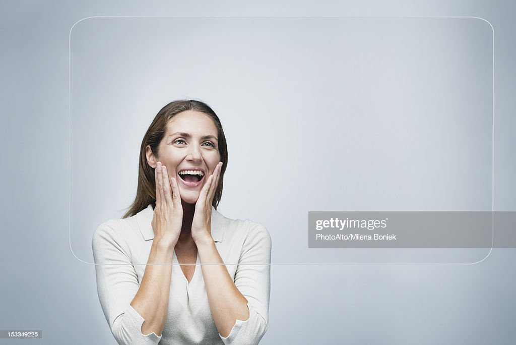 Woman looking at large transparent touch screen with surprised expression on face : Stock Photo