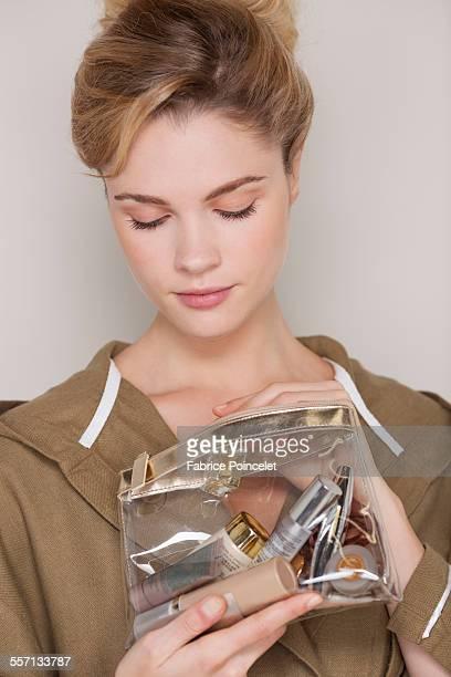 Woman looking at makeup bag