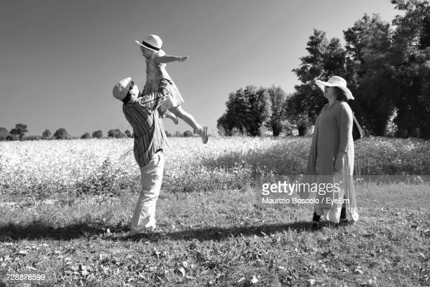 Woman Looking At Man Holding Aloft Daughter On Field Against Clear Sky