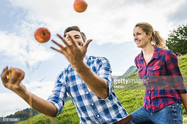 Woman looking at man juggling apples