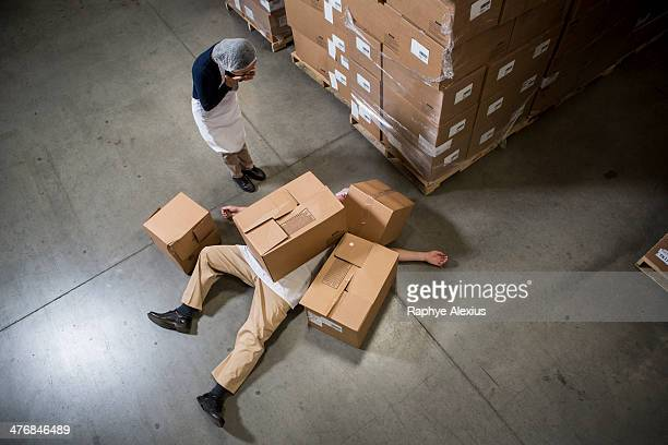 Woman looking at man lying on floor covered by cardboard boxes in warehouse