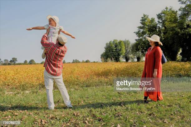 Woman Looking At Man Playing With Daughter While Standing By Agriculture Field Against Sky