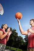 Woman looking at man spinning basketball on finger