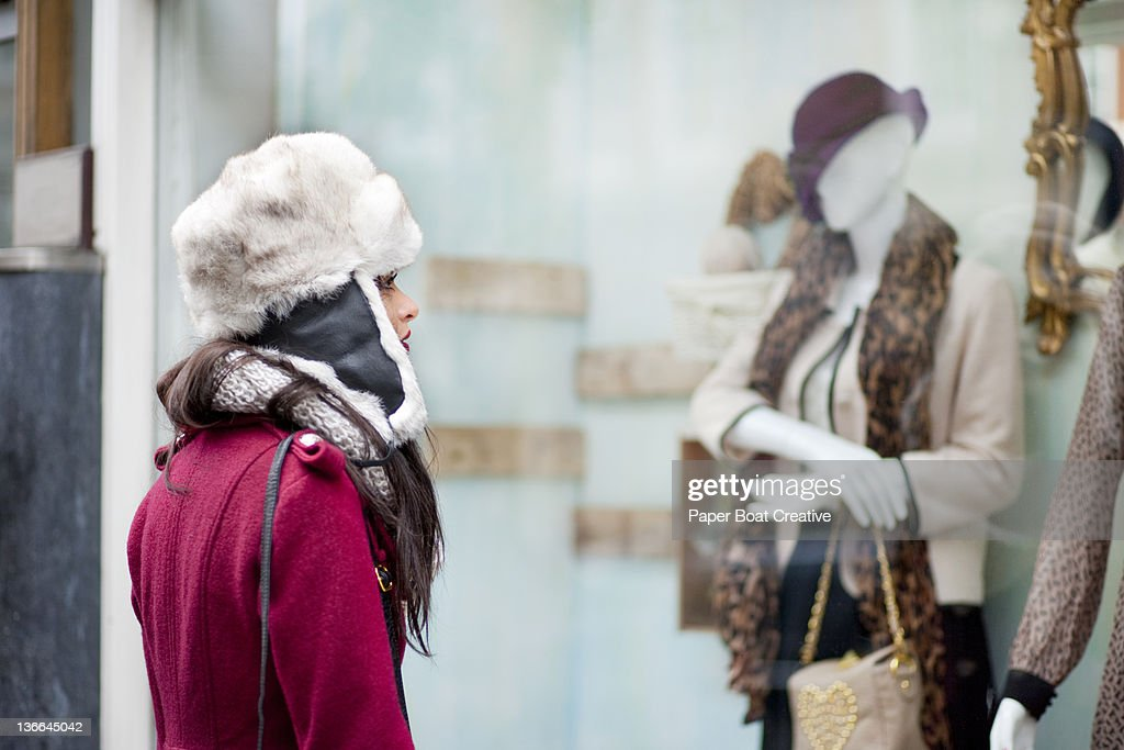 Woman looking at manequin in the window shop : Stock Photo