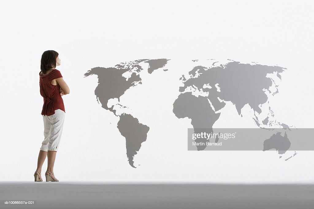 Woman looking at map of world on clear acrylic sheet : Stock Photo