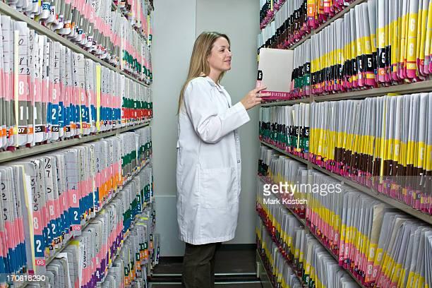 Frau auf der Suche in medizinischen Aufzeichnungen-Heilbehandlung Diagrammen