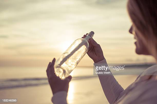 Woman looking at message in bottle.