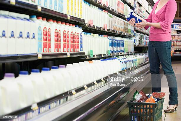 Woman looking at milk carton in supermarket, low section