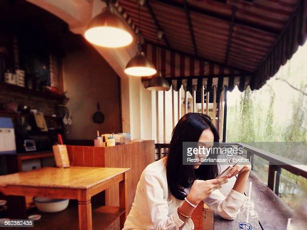 Woman Looking At Mobile Phone At Home