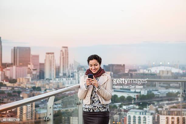 Woman looking at mobile phone, city in background.