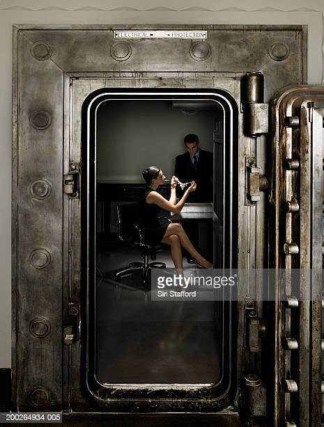 Woman looking at necklace inside vault