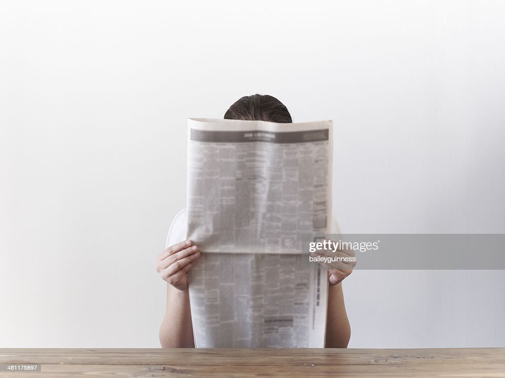 Woman looking at newspaper : Stock Photo