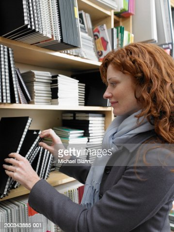 Woman looking at note books in shop, profile