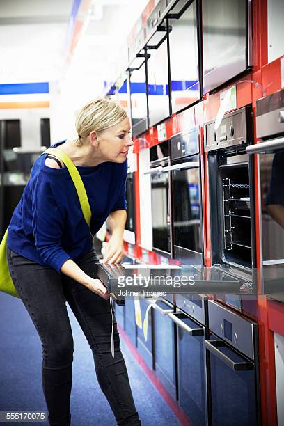 Woman looking at oven in shop