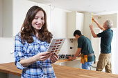 Woman Looking At Paint Chart In New Kitchen