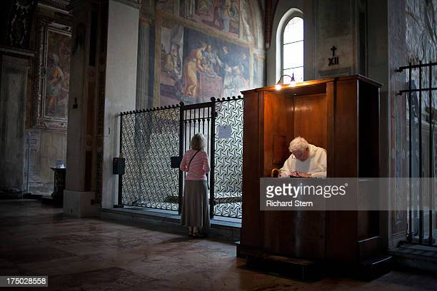 CONTENT] woman looking at painting priest in confessional church cathedral prayer meditation religion Catholic peace peaceful calm spiritual Milan...