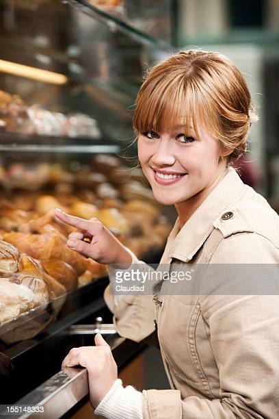 Woman looking at pastry behind window