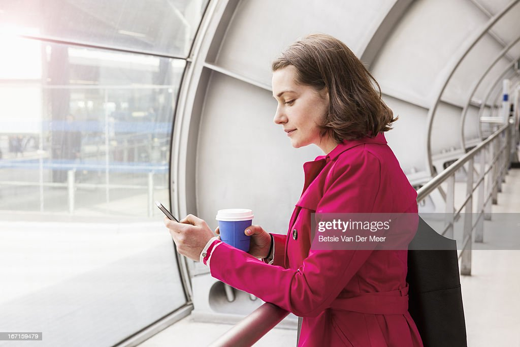 Woman looking at phone waiting in station. : Stock Photo