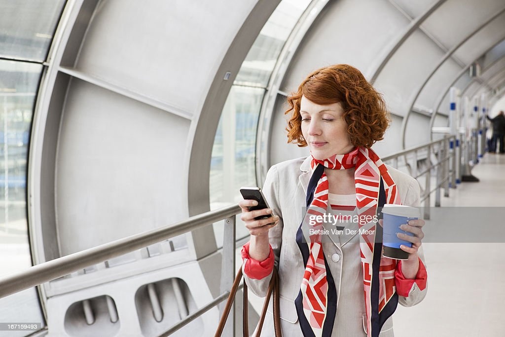 Woman looking at phone walking in station. : Stock Photo