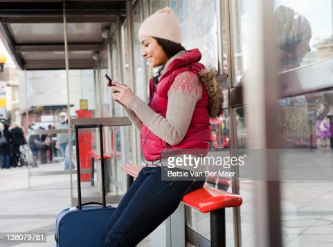Woman looking at phone, while waiting for bus.