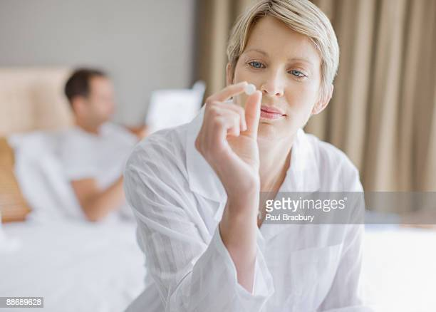 Woman looking at pill