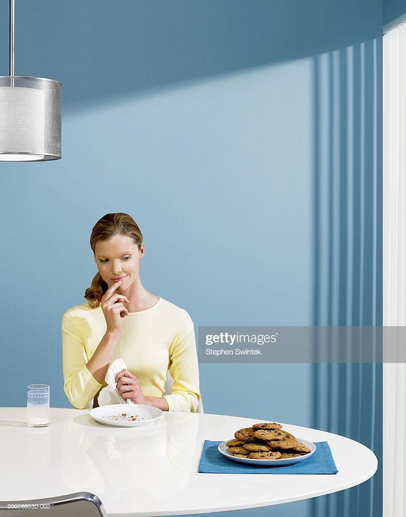 Woman looking at plate of cookies : Stock Photo