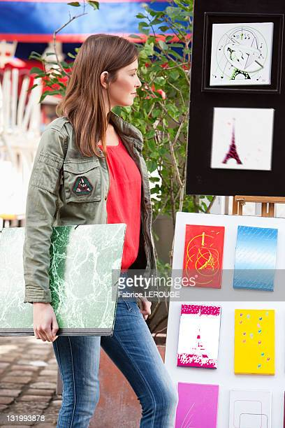 Woman looking at postcards of Eiffel Tower at a market stall, Paris, Ile-de-France, France