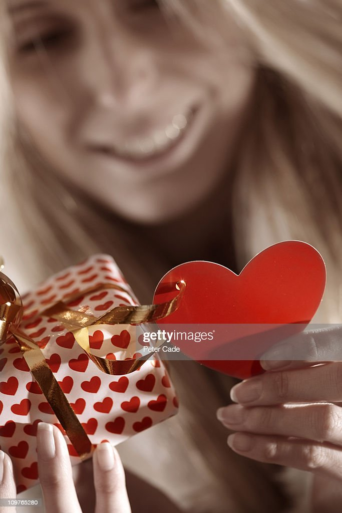 woman looking at present wrapped in heart paper : Stock Photo