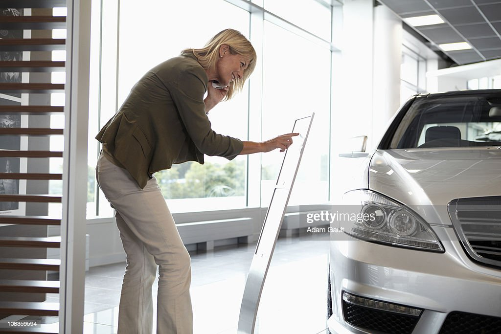 Woman looking at price list for new car in showroom