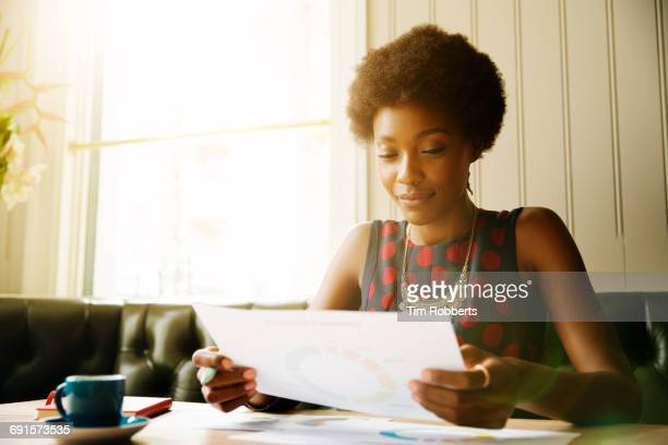 Woman looking at print out, working.