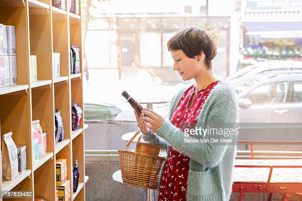 Woman looking at product  ingredients in shop.