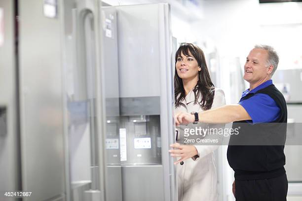 Woman looking at refrigerators in showroom