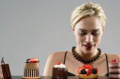 Woman looking at row of tempting desserts